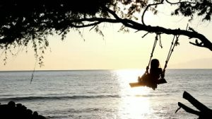 stock-footage-a-little-girl-swings-back-and-forth-on-a-rope-swing-looking-out-over-the-ocean-medium-shot